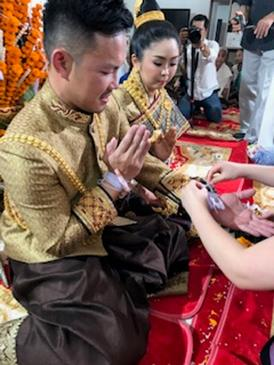 新郎新婦の手首に白い木綿の糸が結ばれます(筆者撮影)